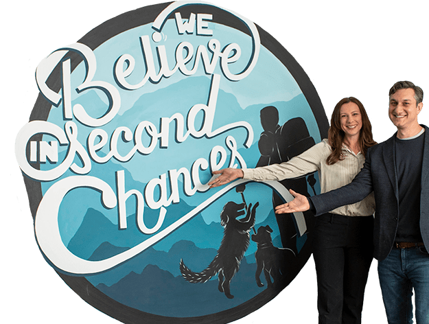 "two professionals beside a mural reading ""We believe in second chances"""